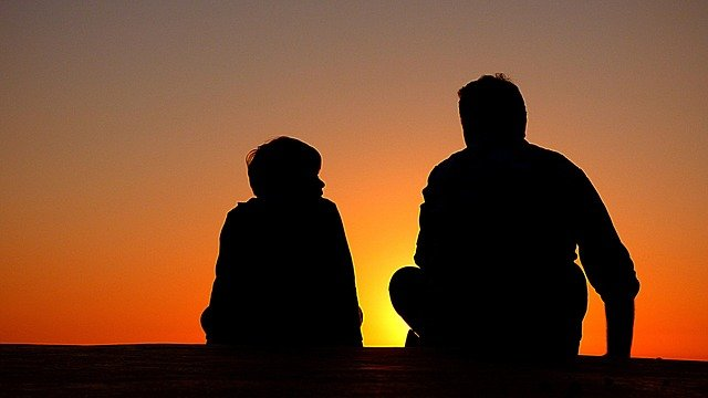 """An imgae of a man and boy sitting in watching the setting sun. Image by <a href=""""https://pixabay.com/photos/?utm_source=link-attribution&utm_medium=referral&utm_campaign=image&utm_content=1082129"""">Free-Photos</a> from <a href=""""https://pixabay.com/?utm_source=link-attribution&utm_medium=referral&utm_campaign=image&utm_content=1082129"""">Pixabay</a>"""